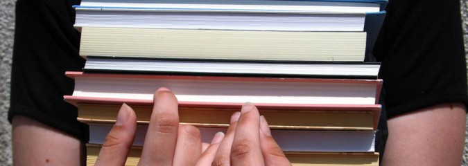 Student's hands holding stack of books, Source: rgbstock.com