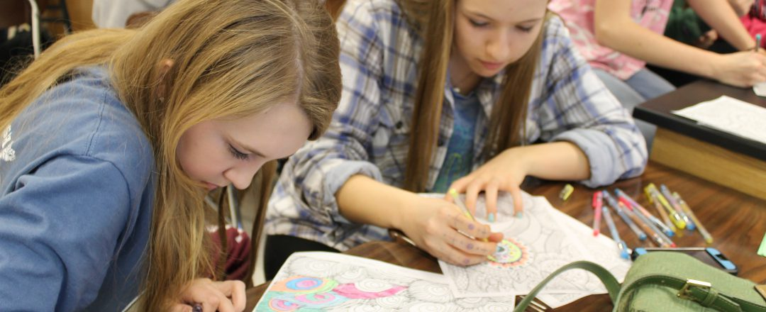 Two girls coloring in class during a mindfulness exercise
