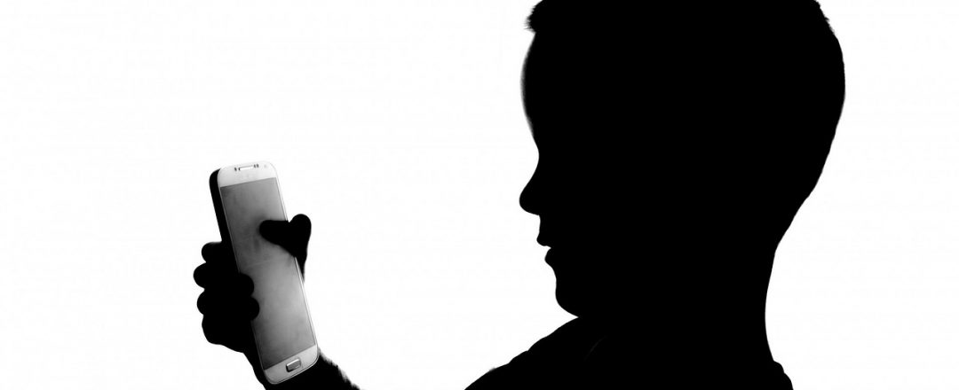 Silhouette of a young child holding a smart phone.
