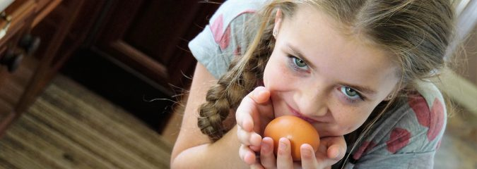 Young girl holding an orange up to her mouth, about to eat it