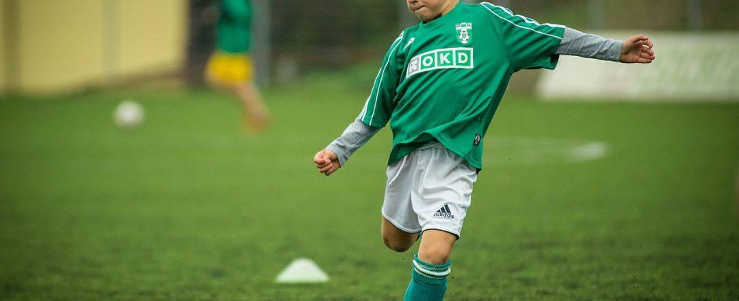 A boy kicks a soccer ball.