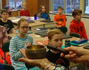 Anne Killian-Russo taps the Tibetan singing bowl