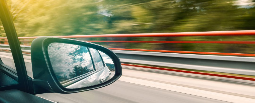 Side-view mirror of car visible, as car speeds down a highway
