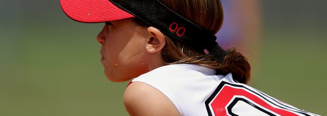 Young girl playing softball gets ready to pitch the ball