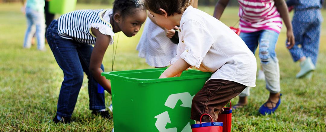 Children volunteering in park gathering recycling