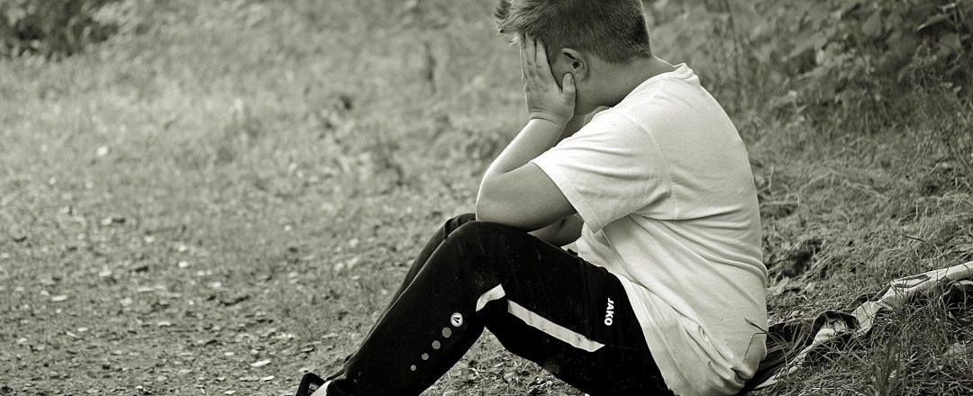Boy sitting on the ground holding his head in grief
